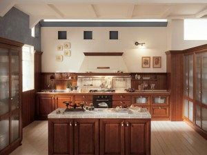 ACANTO - klasična kuhinja koja ima velike mogučnosti slaganja elemenata po mjeri prostora. Vratnica u smeđoj boji, izrađena je od drva debljine 30 mm., sa velikim izborom radnih ploča i ručkica. Na dva bočna zida kuhinje su elementi sa staklom, tipa vitrine, dok su ravno na glavnom zidu sudoper ispod elementa sa dvoje vrata, pa ploča za kuhanje ispod koje je pečnica, a iznad koje je velika napa. Kombinirani su i bazni elementi sa plitkim i dubokim ladicama. Na zidu je drvena rebrasta ploča, koja štiti zid umjesto zidnih pločica.