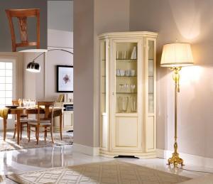 Klasična kutna vitrina, izrađena od masivnog drva, lakirana u krem boju sa zlatnim detaljima. Može se naručiti i u drugim bojama.