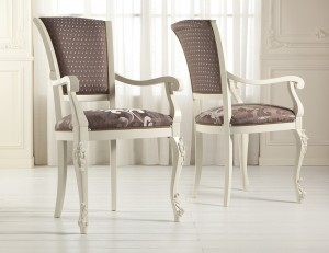 Klasična stolica sa rukonaslonima, izređena od masivnog drva, te izrezbarena, lakirana u bijelu boju, leđa i sjedište presvučeni u tekstil. Može se naručiti i u drugim bojama drva i drugim materijalima.