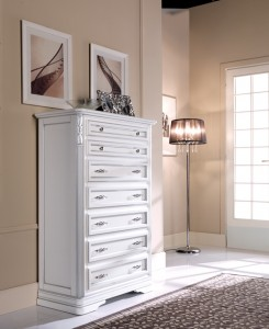 Klasični ladičar sa sedam ladica izrađen od masivnog drva, bojan u bijelu boju sa srebrnim detaljima. Može se naručiti i u drugim bojama.