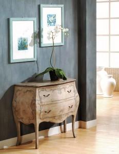 Klasični ladičar sa dvije ladice. Izrađena je od masivnog drva zaobljenog oblika, farban u antik krem boju sa cvijetnim aplikacijama. Može se naručiti i u drugim bojama.