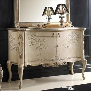 Klasična komoda baroknog stila. Bojana u krem boju sa cvijetnim dekorom. Može se naručiti u drugim bojama sa raznim drugim dekorima ili bez.