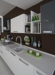 Moderna kuhinja na kojoj se vidi detalj radne ploče, sudoperra i slavine u bijeloj boji.