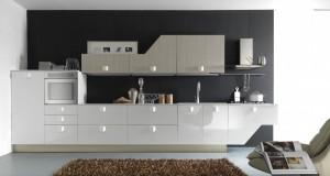 Moderna kuhinja od mediapana i melamina, bojana u sjajno bijelu boju u kombinaciji sa bojom hrasta u finituri tranche'. Kolona za frižider i kolona za pećnicu su u sjajno vijeloj boji sa baznim elementima ladica, sudoperom i pločom za kuhanje. Gornji, viseći elementi su u boji hrasta, ispod kojih su neonska svijetla.