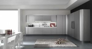 Moderna kuhinja od mediapana, bojana u mat sivu boju titanium. Radna ploča je u bijeloj boji, ispod visećih elemenata su ugređena neonska svjetla. Kompozicija je kutna sa zaobljenim završetkom kolone.