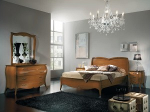 Klasična spavaća soba, bojana u boju svijetlog oraha, izrađena od masivnog drva. Noćni ormarić sa tri ladice, klasični krevet za dvije osobe, komoda sa četiri ladica i ogledalo u kompletu su elementi koji čine komplet ove klasične spavaće sobe. Može se naručiti u drugim bojama drva i drugim veličinama.