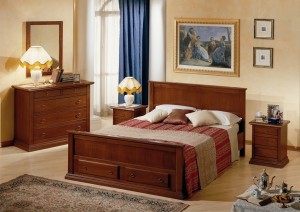 Klasična spavaća soba, bojana u boju oraha, izrađena od masivnog drva. Noćni ormarić sa tri ladice, klasični krevet za dvije osobe, komoda sa četiri ladice i ogledalo u kompletu, su elementi koji čine komplet ove klasične spavaće sobe. Može se naručiti u drugim bojama drva i drugim veličinama.