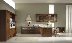 NATASHA - klasična kuhinja po mjeri Vašeg prostora, sa drvenim vratnicama u svijetloj boji lješnjaka. Krem radna ploča sa drvenim rubom, zlatne ručkice i klasični elektro aparati daju toplinu ovoj drvenoj kuhinji. Ispod nape je element sa ladicama na kojem je ploča za kuhanje od koje u desno ide kutni element sa vratima iznad kojeg je sudoper. Dubina radne ploče je proširena kako bi sa druge strane dobili šank sa dvije barske stolice. Viseći elementi su razigrani, sa ili bez stakla, sa iznad ukrasnim klasičnim okvirom. Na zidu pored, istiću se visoki elementi stilske kuhinje sa prostrom za ugradbenu peć i frižider.
