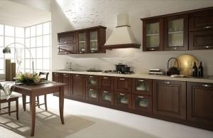 NATASHA - klasična kuhinja po mjeri Vašeg prostora, sa drvenim vratnicama u tamnoj boji lješnjaka. Krem radna ploča visine 4 cm., srebrne ručkice i klasični elektro aparati daju toplinu ovoj drvenoj kuhinji. Ispod nape su elementi sa ladicama na kojima je ploča za kuhanje od koje su desno i lijevo elementi sa vratima za sudoper, perilicu posuđa i elementi za posuđe. Viseći elementi, sa ili bez stakla, su klasičnih dimenzija iznad kojih je ukrasni klasični okvir. Ispred stilske kuhinje je drveni stol sa stolicama u istoj boji kuhinje.