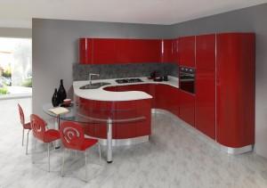 ODESSA - moderna kuhinja od mediapana, sa velikim mogučnostima slaganja elemenata. Nas slici je prikazana kuhinja u vratnicama crvene boje u visokom sjaju, dok je radna ploča bijele boje. Kuhinja je napravljena po mjeri prostora u kutnoj verzji sa elementima zaobljenih linija. Sa desne strane je kolonom za frižider i pećnicu, u sredini ploča za kuhanje iznad koje je napa, dok je s ljeve strane sudoper i perilica posuđa. Sa vanjske strane zaobljenog elementa je iskombinirani stakleni stol za ručavanje sa crvenim stolicama u kompletu.