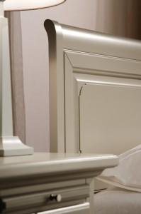 Detalj zaglavlja bračnog kreveta i ladice od nočnog ormarića, bojanih u krem boju.