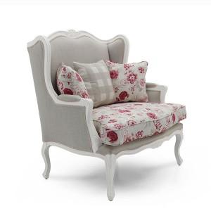 Klasična fotelja sa drvneim okvirom u bijeloj boji. Presvučena u materijal sive boje, leđni i sjedeći jastuci u cvijetnom uzorku. Može se naručiti u drugim bojama drva i materijala.