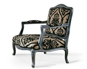 Klasična fotelja sa drvenim okvirom u sivoj boji, presvučena u materijal sa cvijetnim uzorkom u bež i crnoj boji. Može se naručiti u drugim bojama drva i drugim materijalima.