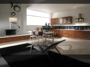 STEFANY – kuhinja po mjeri Vašeg prostora, koja iz modernog dnevnog dijela sa ljeve strane, prelazi u klasičnu kuhinju sa desne strane. Drvena kuhinja sa klasičnim elementima i dnevni dio sa niskim elementima u boji su trešnje, sa kromiranim ručkicama i bijelom radnom pločom koji daju prostoru moderan i opuštajući stil. Za upotpunjavanje prostora dodane su stolice i stol ravnih linija sa jednom metalnom nogom na desnom boku, dok je drugi bok stola pričvršćen na zid.