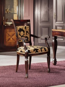 Klasična drvena stolica sa rukonaslonima u boji oraha, sjedište i leđa u tkanini. Može se naručiti u drugim bojama drva i drugim tkaninama.