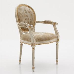 Klasična drvena stolica sa rukonaslonima, lakirana u bijelu boju sa patinom i detaljima tapkanim sa zlatnim listićima. Sjedište i leđa u tkanini. Može se naručiti u drugim bojama drva i tkaninama.