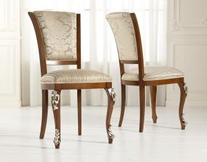 Klasična stolica, izređena od masivnog drva, te izrezbarena, u boju oraha, leđa i sjedište presvučeni u tekstil. Može se naručiti i u drugim bojama drva, te drugim materijalima.
