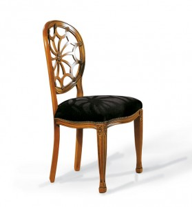Klasična drvena stolica sa rukonaslonima, lakirana u svijetlu boju oraha, sjedište u tkanini. Može se naručiti u drugim bojama drva i drugim tkaninama.