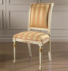 Klasična drvena stolica lakirana u patiniranu bijelu boju sa zlatnim detaljima, sjedište i leđa u tkanini. Može se naručiti u drugim bojama drva i drugim tkaninama.