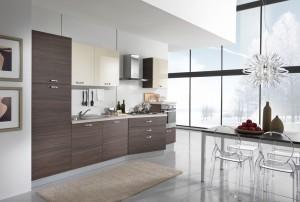 VELVET - moderna kuhinja od mediapana, sa velikim mogučnostima slaganja elemenata. Nas slici je prikazana kuhinja sa kolonom za frižider sa ljeve strane, do nje sudoper i perilica posuđa, ploča za kuhanje u izbočenom elementu iznad koje je napa, dok je s ljeve strane niža kolona sa pećnicom unutra. Iznad svih bagni elmenata su viseći elementi u visokom sjaju, dok su ostale vratnice kuhinje u tranchè smeđoj boji. Kuhinja po mjeri za sve prostore i sve veličine.