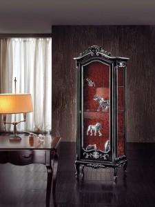 Klasična vitrina sa jednim vratima, izrađena od masivnog drva, bojana u antik crnu boju sa bijelim brisevima. Može se naručiti u različitim drugim bojama.