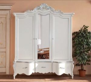 Klasični ormar bojan u bijelu boju sa zlatnim detaljima. Tri vrata i tri ladice.