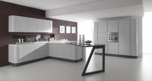 Moderna kuhinja od mediapana, bojana u mat sivu boju. Radna ploča je u bijeloj boji. Kompozicija je kutna sa zaobljenim završetkom na kojeg se veže šank u crnoj boji sa nogom otvorenog tipa. Na drugom zidu su frižider i pećnica u kolonama.