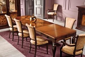 Klasična blagavaona izrađena od masivnog drva u boji moka sa dodacima svijetlog oraha. Klasični stol sa pločom u intarzijama, 250x90 cm. (zatvoreni 170x90). U kompletu je klasična stolica sa sjedištem i leđima u tkanini i klasična stolica sa rukonaslonima. Sve se može naručiti u drugim bojama drva i tkanina.