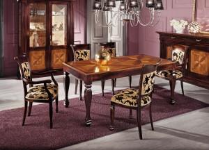 Klasični stol u kompletu sa klasičnim stolicama sa i bez rukonaslona. Ploča stola je izrađena sa interzijama. Sjedište i leđa stolica presvučene su u tkaninu. Može se naručiti u drugim bojama drva i drugim tkaninama.