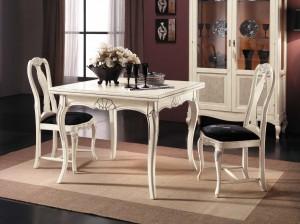 Klasična blagavaona, bojana u antik bijelu boju. Stol je 100x100 cm, i otvara se kao knjiga, njegove otvorene dimenzije su 200x100 cm. U kompletu je klasična stolica sa sjedištem od tkanine. Može se naručiti u bilo kojim drugim bojama drva i tkaninama.