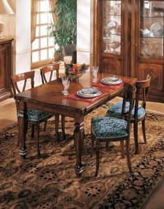 Klasična blagavaona izrađena od masivnog drva u boji oraha. Klasični stol sa pločom u intarziji je veličine 160x100 cm. (otvoreni 240x100). U kompletu je klasična stolica sa sjedištem u tkanini. Može se naručiti u drugim bojama i tkaninama.