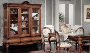 Klasični dnevni dio izrađen od masivnog drva u boji oraha, za Vašu klasičnu ručaonu. Klasična vitrina sa tri staklena vrta i tri ladice u kompletu klasični stol sa klasičnim stolicama. Stolice su presvučene u tkaninu cvijetnog uzorka u kombinaciji sa drvom.