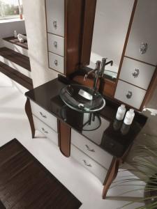 Klasični lavabo u staklu sa 4 ladice. Struktura drva bojana u klasičnu smeđu boju, dok su fronte ladica bojane u sivu boju. Ploča lavaboa je u crnom staklu, dok je lavabo od prozirnog stakla, okruglog oblika.