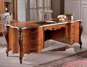Klasični pisaći stol izrađen od masivnog drva, bojan u boju oraha. Pisaći stol ima sedam ladica i prekrasne noge izrađene sa cvijetnim uzorkom.